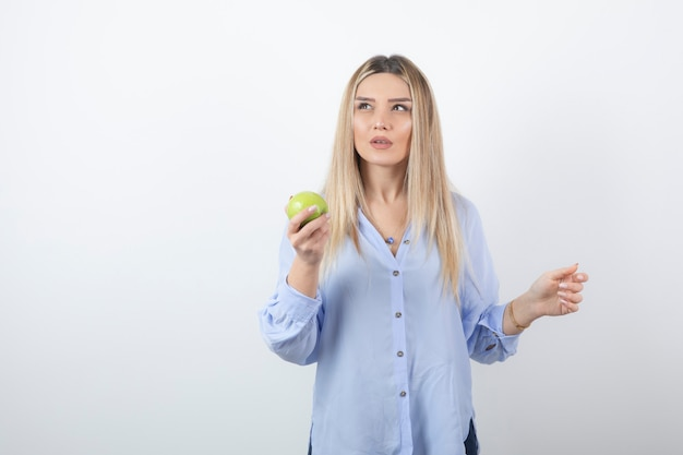 Portrait of a pretty attractive woman model standing and holding a green fresh apple .