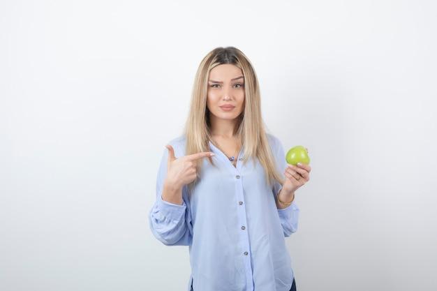 Ritratto di un modello di donna piuttosto attraente in piedi e che punta a una mela fresca verde.