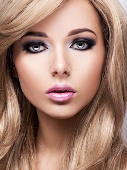 Ritratto di giovane donna abbastanza attraente con trucco luminoso. bello dai capelli castani.