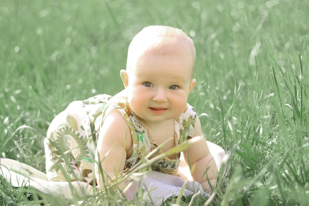 Portrait of pretty baby on the lawn on a summer day
