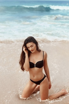 Portrait of pretty beautiful fashion woman in black bikini posing in summer near the sea and blue sky. young girl with tanned sexy body in swimwear with copy space. summer lifestyle. vacation
