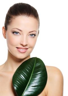 Ritratto di donna sorridente abbastanza bella con foglia verde vicino al suo viso