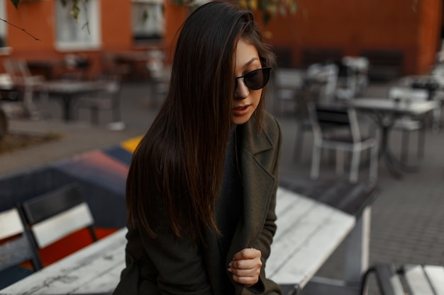 Portrait of a pretty beautiful and young brunette girl in a stylish  oversized coat and sunglasses sitting in an outdoor cafe. outdoor lifestyle fashion.