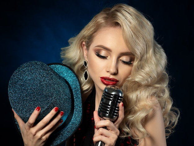 Portrait of pretty blond female singer holding retro styled microphone