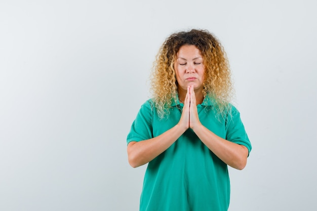 Portrait of pretty blond lady keeping hands together while praying in green polo t-shirt and looking peaceful front view