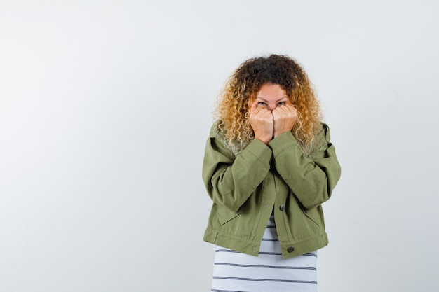 Ritratto di donna abbastanza bionda che nasconde il viso dietro le mani in giacca verde e guardando spaventato vista frontale