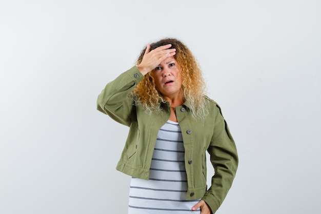 Portrait of pretty blond woman keeping hand on head in green jacket and looking forgetful front view
