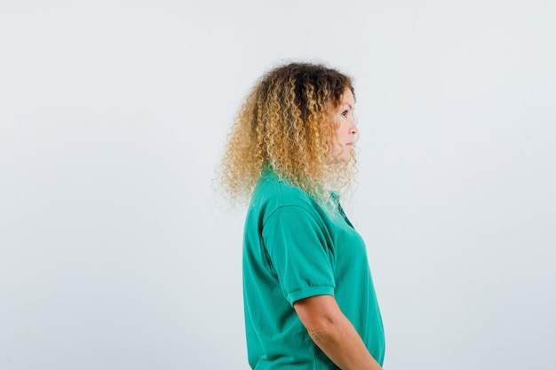 Portrait of pretty blond woman looking far away in green polo t-shirt and looking silent