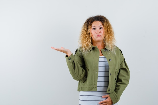 Portrait of pretty blond woman spreading palm aside in green jacket and looking puzzled front view