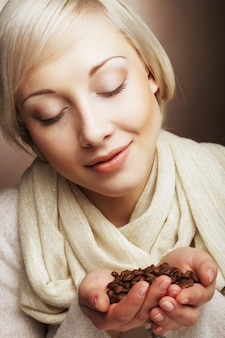 Portrait of pretty blonde girl hold coffee beans in hands