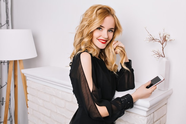 Portrait of pretty blonde girl with smartphone in hands in bright room with nice, modern white interior, standing against fake fireplace, looking. wearing glamurus black dress.