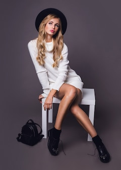 Portrait of pretty blonde model sitting on table in white casual warm knitted sweater and black hat
