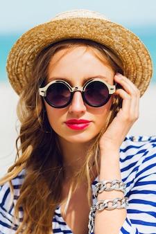 Ritratto di donna alla moda abbastanza bionda in cappello di paglia e occhiali da sole
