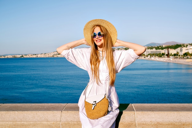 Portrait of pretty blonde tourist woman posing in french riviera, wearing fashionable summer dress