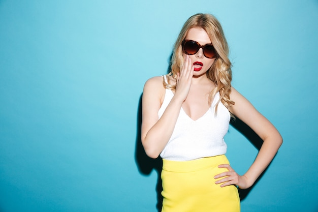 Portrait of a pretty blonde woman wearing sunglasses and posing