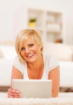 Ritratto di donna abbastanza bionda con tavoletta digitale a casa