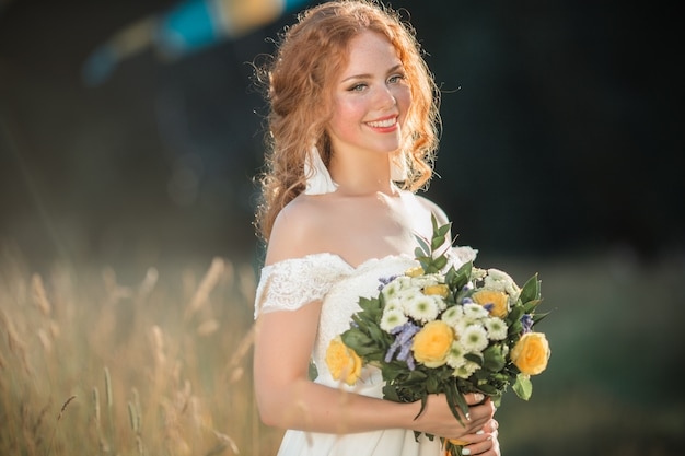 Portrait of pretty bride with freckles in a field with bridal bouquet of wildflowers