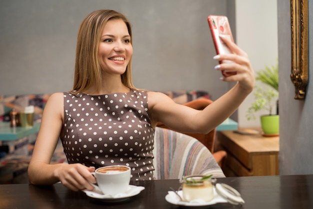 Portrait of pretty brown-haired girl making selfie on her mobile phone at restaurant table