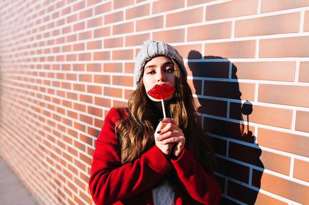 Portrait pretty brunette girl with lollipop lips on wall  outside. she wears knitted hat, red coat.