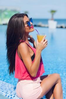 Ritratto di una bella ragazza bruna con i capelli lunghi è seduto vicino alla piscina. tiene da bere e tiene gli occhi chiusi.