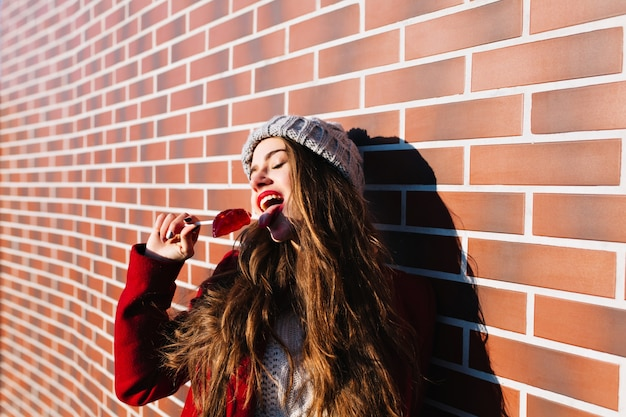 Portrait pretty brunette girl with long hair on wall  outside. she wears knitted hat, red coat. licks caramel red lips, keeps eyes closed.