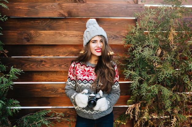 Ragazza graziosa del ritratto del brunette con le labbra rosse in cappello lavorato a maglia e guanti che tengono la macchina fotografica sui rami verdi circondano in legno