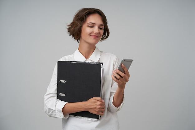 Ritratto di bella donna castana con taglio di capelli corto che tiene cartella con documenti e digitando un messaggio sul suo telefono cellulare, essendo di buon umore, isolato
