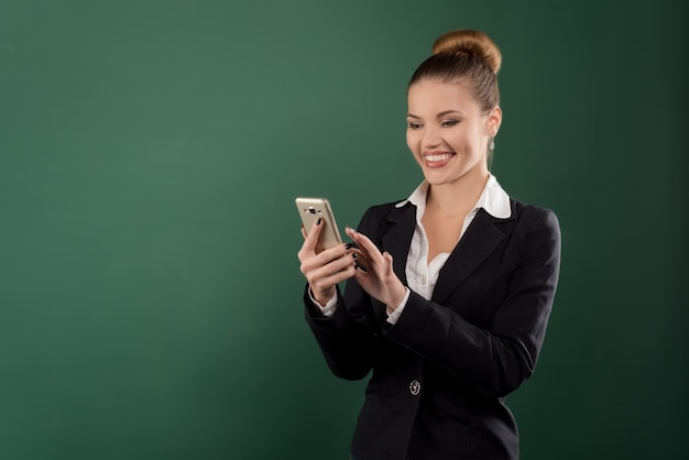Portrait of pretty business brown-haired lady reading something on her mobile phone at green background