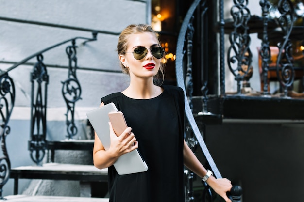 야외 계단에 검은 드레스에 초상화 예쁜 사업가. 그녀는 카메라를 찾고 있습니다.
