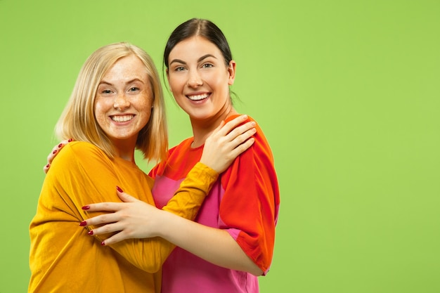 Portrait of pretty charming girls in casual outfits on green studio