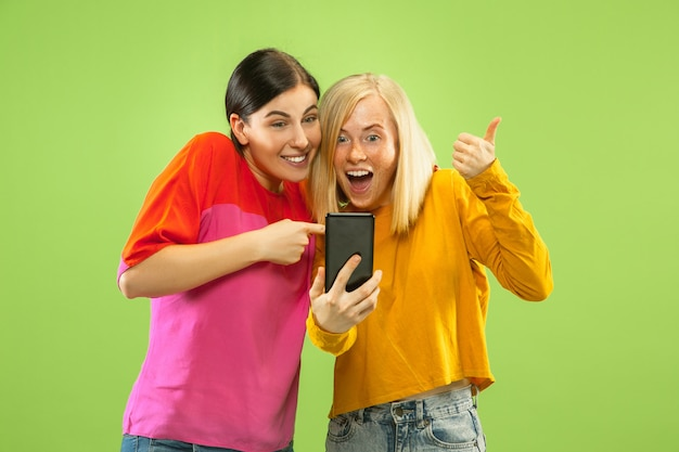 Portrait of pretty charming girls in casual outfits isolated on green studio background. girlfriends or lesbians making selfie. concept of lgbt, equality, human emotions, love, relation.