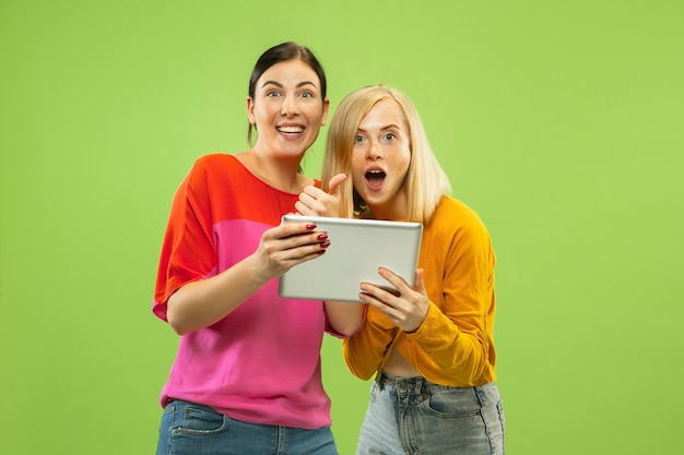 Portrait of pretty charming girls in casual outfits isolated on green studio background. girlfriends or lesbians using a tablet for fun or payments. concept of lgbt, human emotions, love, relation.