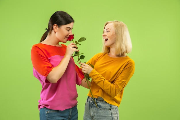 Ritratto di ragazze abbastanza affascinanti in abiti casual isolati su sfondo verde studio. due modelli femminili come amiche o lesbiche. concetto di lgbt, uguaglianza, emozioni umane, amore, relazione.