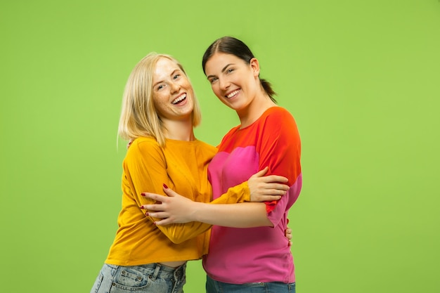 Portrait of pretty charming girls in casual outfits isolated on green studio background. two female models as a girlfriends or lesbians. concept of lgbt, equality, human emotions, love, relation.