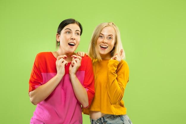 Ritratto di ragazze abbastanza affascinanti in abiti casual isolato sulla parete verde dello studio
