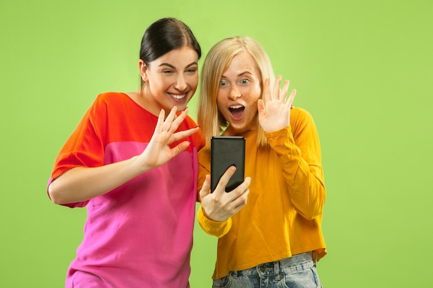 Portrait of pretty charming girls in casual outfits isolated on green wall. girlfriends or lesbians making selfie. concept of lgbt, equality, human emotions, love, relation.