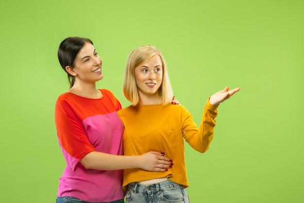 Ritratto di ragazze abbastanza affascinanti in abiti casual isolati su verde