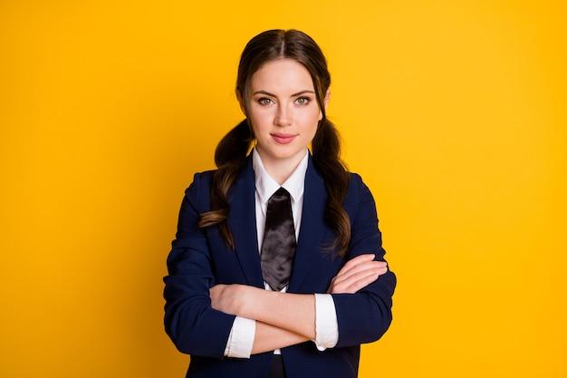 Portrait of pretty charming schoolgirl folded arms