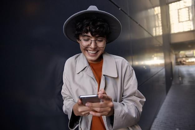 Ritratto di donna castana abbastanza allegra con l'acconciatura casual che si appoggia sul muro urbano nero e controlla i social network con il suo smartphone, indossando abiti eleganti e copricapo