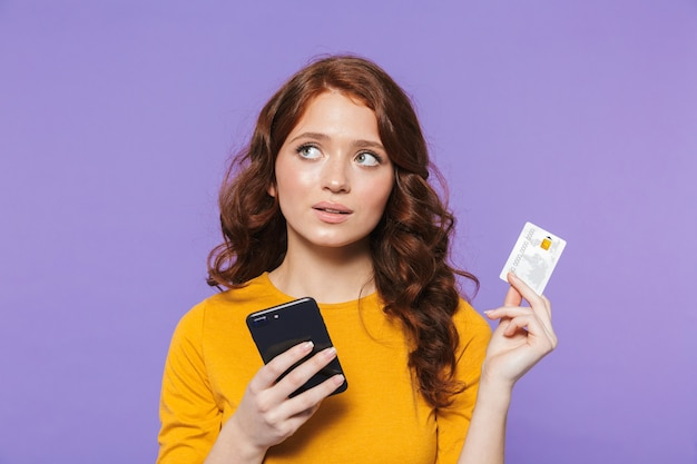 Portrait of a pretty cheerful young redheaded woman standing over violet, using mobile phone, showing credit card