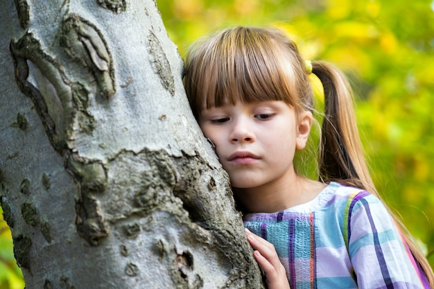 Portrait of pretty child girl leaning to a tree trunk in autumn park relaxing. cute female kid enjoying warm fall weather in forest.