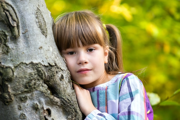 Portrait of pretty child girl leaning to a tree trunk in autumn park relaxing.