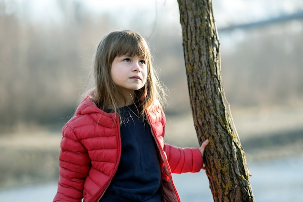 Portrait of a pretty child girl standing near a tree trunk in autumn outdoors.