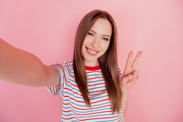 Portrait of pretty confident friendly lady take selfie show v-sign on pink background