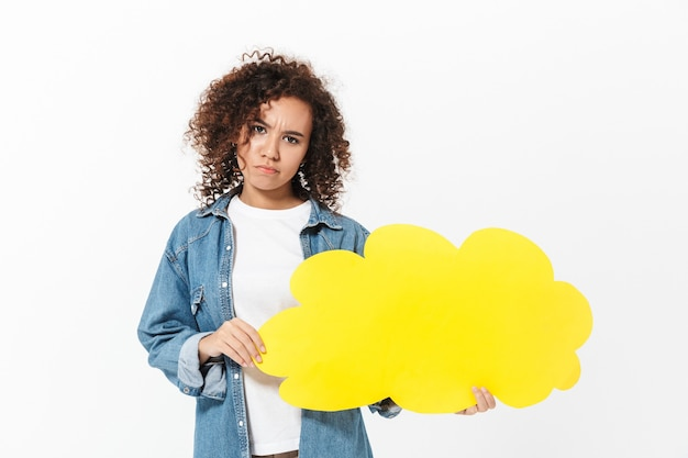 Portrait of a pretty confused casual african girl standing isolated over white wall, holding speech bubble