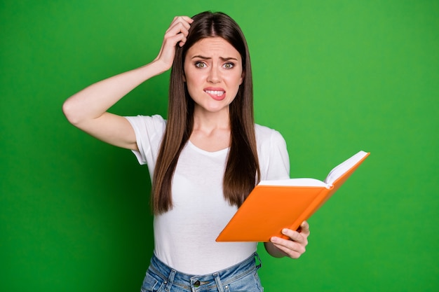 Portrait of pretty confused intellectual girl nerd reading book wear casual t-shirt isolated on green background