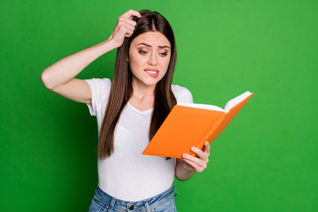 Portrait of pretty confused young lady read book touch head wear casual t-shirt isolated on green background