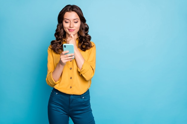 Portrait of pretty curly lady holding telephone hands thinking over creative post text arm on chin wear yellow shirt trousers .