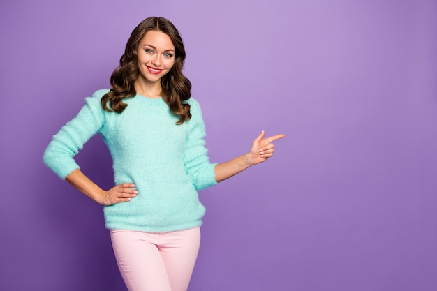 Portrait of pretty curly lady indicating finger empty space advising black friday low shopping prices wear casual teal fluffy pullover pink pastel pants.