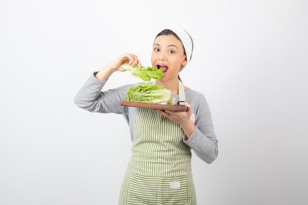 Ritratto di una donna abbastanza carina che mangia lattuga fresca Foto Gratuite
